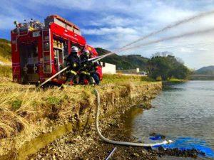 川の水を放水する消防隊