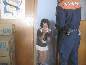 煙の中を避難する児童