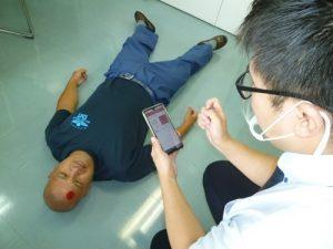 怪我人(左)を見つけ、Net119で通報する利用者(右)